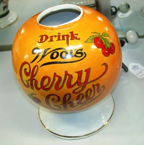 A Wool's Cherry Cheer soda fountain syrup dispenser in pumpkin color, possibly one of a kind.
