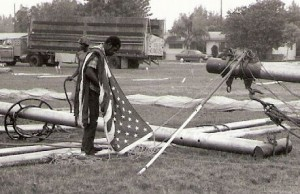 A bale ring on a big top center pole. A worker is preparing and U.S. flag to mount on top of one of the big top poles. Both of these photos were taken in the 1970s on the Clyde Beatty-Cole Bros. Circus.