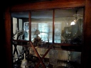 The original glass in the cabinet is 19th century cylinder glass that has the delicious distortions shown in the reflection. It would be a shame to replace the two missing panes with perfectly clear modern glass. 19th-century cylinder glass is available from a number of sources.