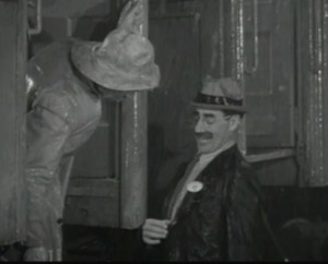 As Groucho Marx tries to board the circus train he shows his brother Chico his badge.