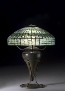 This 18-inch leaded glass geometric shade in blue-green mottled glass, supported by a rare Tiffany bronze base of urn form with paw feet on flat disk, sold for $17,825 (including the buyer's premium) in an October 2006 auction.