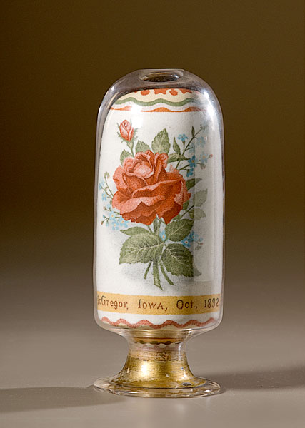 A blown oblong footed bottle with polished pontil. Geometric decoration throughout with one side featuring a rosebud nosegay above a yellow band with the caption, McGregor, Iowa, Oct. 1892.