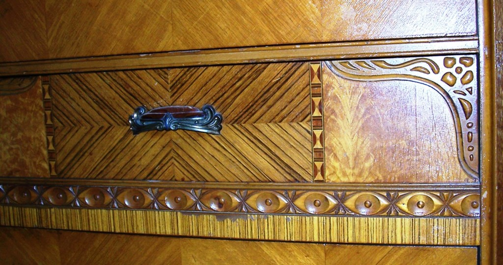 """The vertical striped banding below the drawer looks like zebra wood veneer but it is printed paper known as """"veneerite."""" You can see where it has worn off in the middle section."""