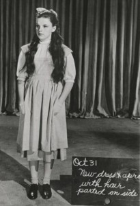"Judy Garland modeling the ""test"" dress and pinafore from ""The Wizard of Oz"" during a costume showing."