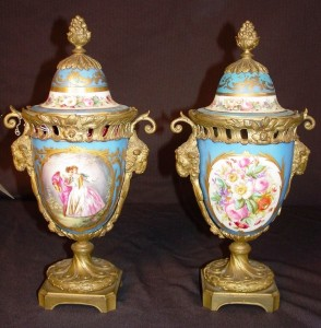 Available for purchase will be a pair of Sevres urns, capped with bronze mounting, ram's head and painted scene of French royalty, marked Sevres.
