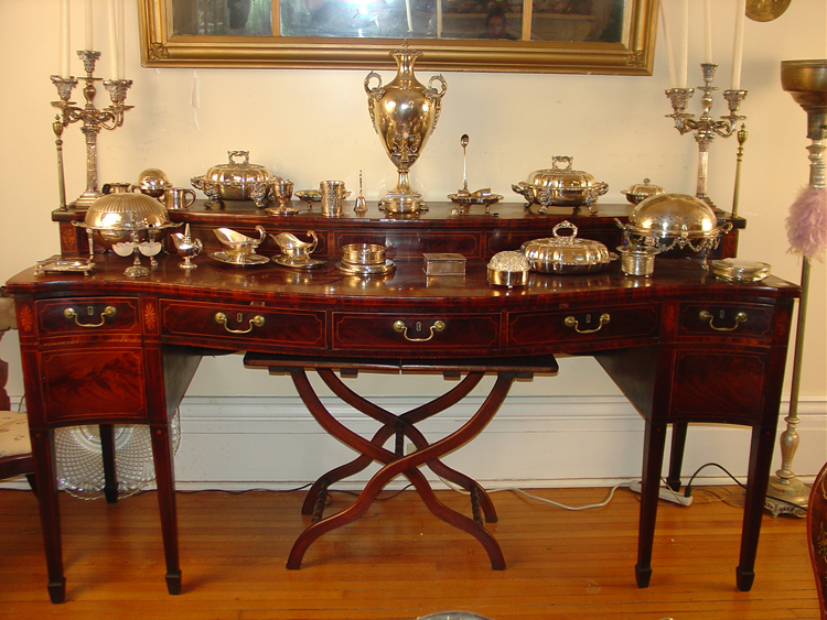 This Sheraton-style flame mahogany sideboard with great inlay supports sterling silver pieces.