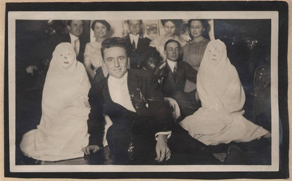Why are there two ghosts in this vintage photo when nobody else is dressed in costume? And who is the goggle-eyed man showcased in front? Collectors of found photography love a mystery. This scratched photo pasted to album paper sold for $25 in July 2014.